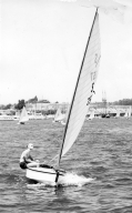 Snowbird class sailboat in Newport Harbor with young man.