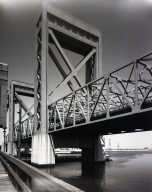 "The old Henry Ford Ave. Bridge, a ""Biscaule"" tilt and counterbalanced bridge to Terminal Island, alongside the Commodore Schuyler Heim Bridge, a lift bridge replacing the Ford Ave. Bridge. Both cross the Cerritos Channel in Long Beach Harbor."