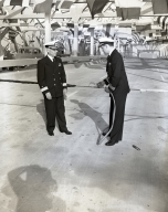 Dedication of the Schuyler F. Heim lift bridge across the Cerritos Channel to the Long Beach Naval Station and the Long Beach Naval Shipyard. L to R, Commodore Schuyler F. Heim and a Navy Commander (with blow torch) cut cable to open bridge to traffic.