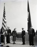 Dedication of the Schuyler F. Heim lift bridge across the Cerritos Channel to the Long Beach Naval Station and the Long Beach Naval Shipyard. Between flags, Commodore and Mrs. Heim at the bronze plaque that tells of the bridge.