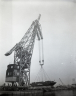 The first lift by the giant German crane at the Long Beach Naval Shipyard. This crane is lifting more than 100 tons of barge filled with seawater as a trial. This crane was one of four floating cranes built by German industries to maneuver in water because their land is very swampy and the ground unable to support large cranes with heavy lifts. It was taken as reparation from the German submarine-building facility at Keil, Germany, and was brought across the Atlantic, through the Panama Canal and up the Pacific Coast to Long Beach, and reassembled here. (The other cranes, taken by England, France and Russia were all lost at sea). Pictures are poor due to very foggy morning.