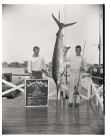 Fred V. Cummings posing with a marlin he caught.