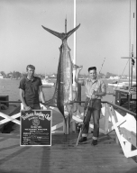 Ens. C. W. Cummings poses with a marlin he caught.