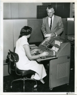 Miss Ruth Head at the IBM Long Beach office operates a IBM card sorter. An IBM alphabetical accounting machine is at left.