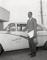 Newport Balboa Savings and Loan employees standing in front of a company car.