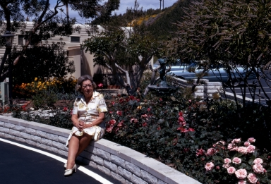 Resident Ruth Blackmore sitting on a wall by her garden.