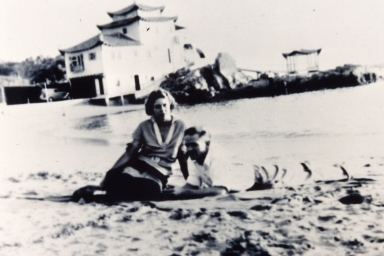 A man and woman on the beach in China Cove, with China House in the background.
