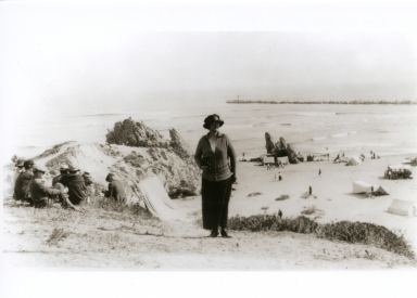 A woman posing for a photograph on the Corona del Mar bluff with China Cove in the background.