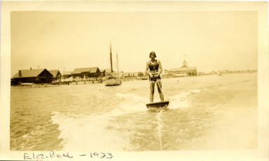 Elizabeth Bell aquaplaning in Newport Harbor.  The Balboa Pavilion and other buildings appear in the background