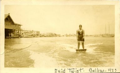 Enid Twist aquaplaning in Newport Harbor.  To the left is the Balboa Pavilion.