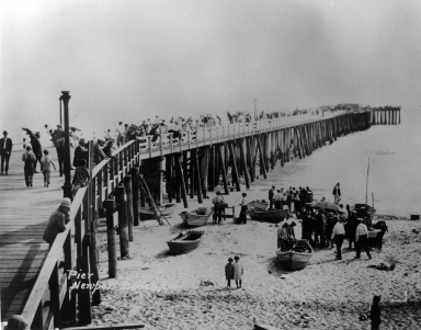 People walking on the Newport pier. To the right, onthe beach are fishermen with their dories.