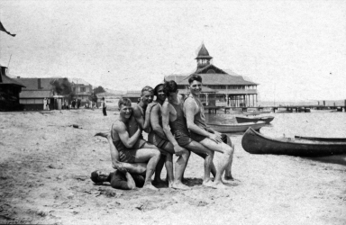 Six young men in bathing suits pose with the Balboa Pavilion in the background