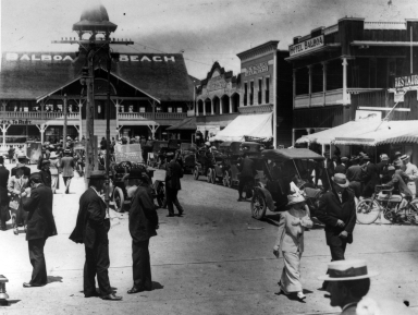 People walking on Main Street with the Balboa Pavilion in the background.
