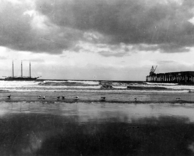 Newport Beach shoreline with large ship in background and pier to the right.