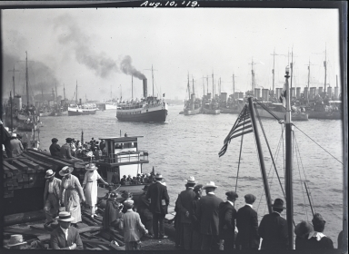 Destroyers docked to right, excursion boat & people in foreground, ships in harbor