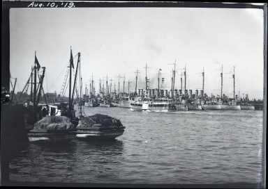 Destroyers docked in rear, excursion boat in center, fishing boats in foreground