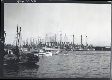 Destroyers docked in rear, excursion boat & fishing boats to left