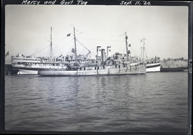 USS Mercy (AH-4) at dock, #18 government tug in foreground