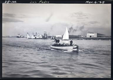 Sailors in shoreboat in harbor, dredger in rear