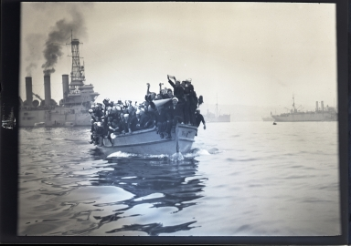 Sailors in shoreboat in harbor, naval ships in background