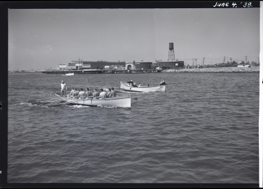 Sailors rowing shoreboats in harbor, warehouses and water tower in background