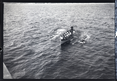 Sailors rowing shoreboat in harbor
