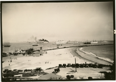 Ships in outer harbor, beach, cars in foreground
