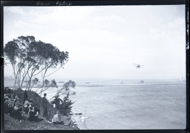 Spectators on shore viewing Pacific Fleet, ships, low flying plane, breakwater