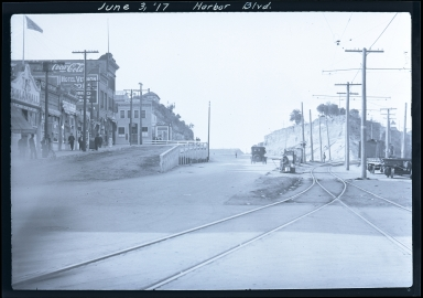 Harbor Boulevard, train tracks, people, cars