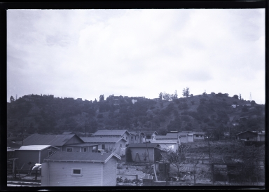 Small houses in foreground, few houses on hillside