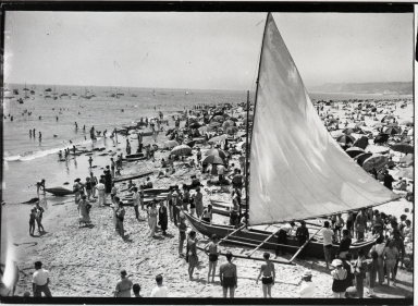 Outrigger sailing canoe on beach, bathers, kayaks; small negative