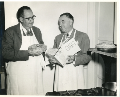 Two men, one holding a pie as the other holds a cookbook.