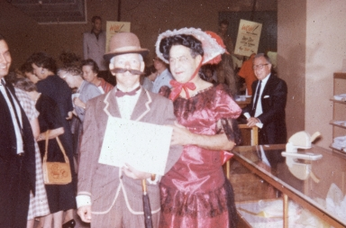 Two men dressed in early-twentieth century clothing at an employee event.