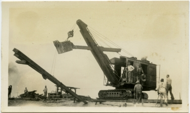 The steam shovel (aboard a flatcar) and crew arrive to finish construction of the west jetty, Newport Harbor.