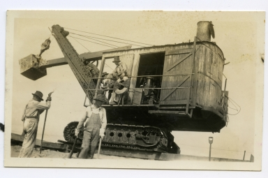 Steam shovel (aboard a flatcar) and crew arrive to finish construction of the west jetty, Newport Harbor.