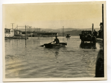 Boy rowing a boat on a flooded street in Newport Beach. Flooding was caused by work on the west jetty of Newport Harbor.
