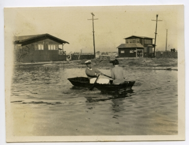 Man rowing a boat with a woman passenger on a flooded street in Newport Beach. Flooding was caused by work on the west jetty of Newport Harbor.