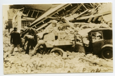Men sifting through debris of unidentified building damaged in Compton [Long Beach] earthquake.