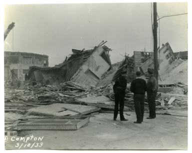 Men surveying earthquake damage to unidentified building in Compton.