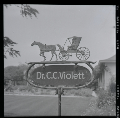 Dr. C. C. Violett's novel office emblem (on sign) depicts horse-and-buggy era that he remembers. Dr. Violett is a longtime Orange County medical doctor.