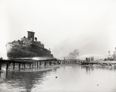 The burned-out hull of the tanker ship, Markay, at Union Oil Co. terminal dock.