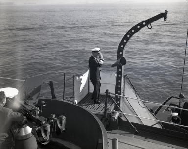"Ceremony aboard Battleship South Dakota to honor Admiral ""Bull"" Halsey as he retires from U.S. Navy Pacific Fleet. This neg shows Halsey saluting the flag as he stands on gangway to leave ship. (November 22)"