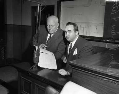 """Famous"" gangster Mickey Cohen and his attorney as they confer in Cohen's first trial in federal court for income tax evasion."