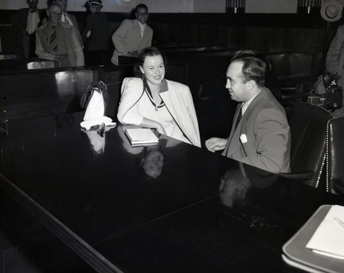 """Famous"" gangster Mickey Cohen and his attorney as they confer in Cohen's first trial in federal court for income tax evasion. Court ""hangers-on"" at back."
