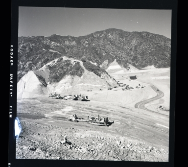 In the 1950's golf became the passion of Southern California, players and great pressure came to bear on politicians to increase places to play; so a mountain was moved to make room to play golf. A cat skinner holds the tiny ball in amusement at the mighty effort for the golf ball.
