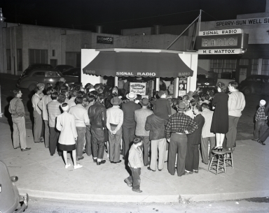 At Atlantic Blvd. and Bixby Road a crowd gathers to watch a black and white TV broadcast on a 10 or 12-inch screen. (Some people brought stools to stand on to get a better view). Mr. M.E. Mattox had an early radio store which also became the first television store in Long Beach. [1946(?) or 1947]