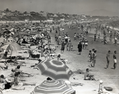 4th of July crowd on the beach viewed from both sides/ends of the Rainbow Pier. The Alamitos Ave. end (east) shows the Villa Riviera and the Pacific Coast Club (upper left in neg), and beach houses. The Pine Ave. end (west) shows roller coaster structure at The Pike, and the strand.