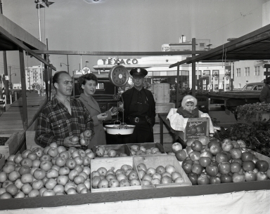"""Open-air """"Farmers' Market"""". (Market Master is wearing military cap with eagle medallion on front.)"""