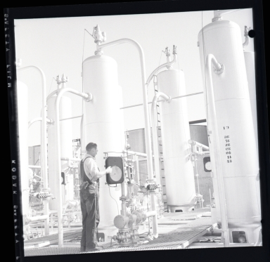 """Long Beach Harbor lease to Richfield. Along the west side of the Los Angeles River flood channel. A very consecrated production site. All pumps were underground and the """"silver tanks"""" (sic) separators from oil & gas. 1946-48 period of harbor oil production and subsidence. (1 of 3)"""