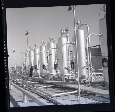 "Long Beach Harbor lease to Richfield. Along the west side of the Los Angeles River flood channel. A very consecrated production site. All pumps were underground and the ""silver tanks"" (sic) separators from oil & gas. 1946-48 period of harbor oil production and subsidence. (1 of 3)"